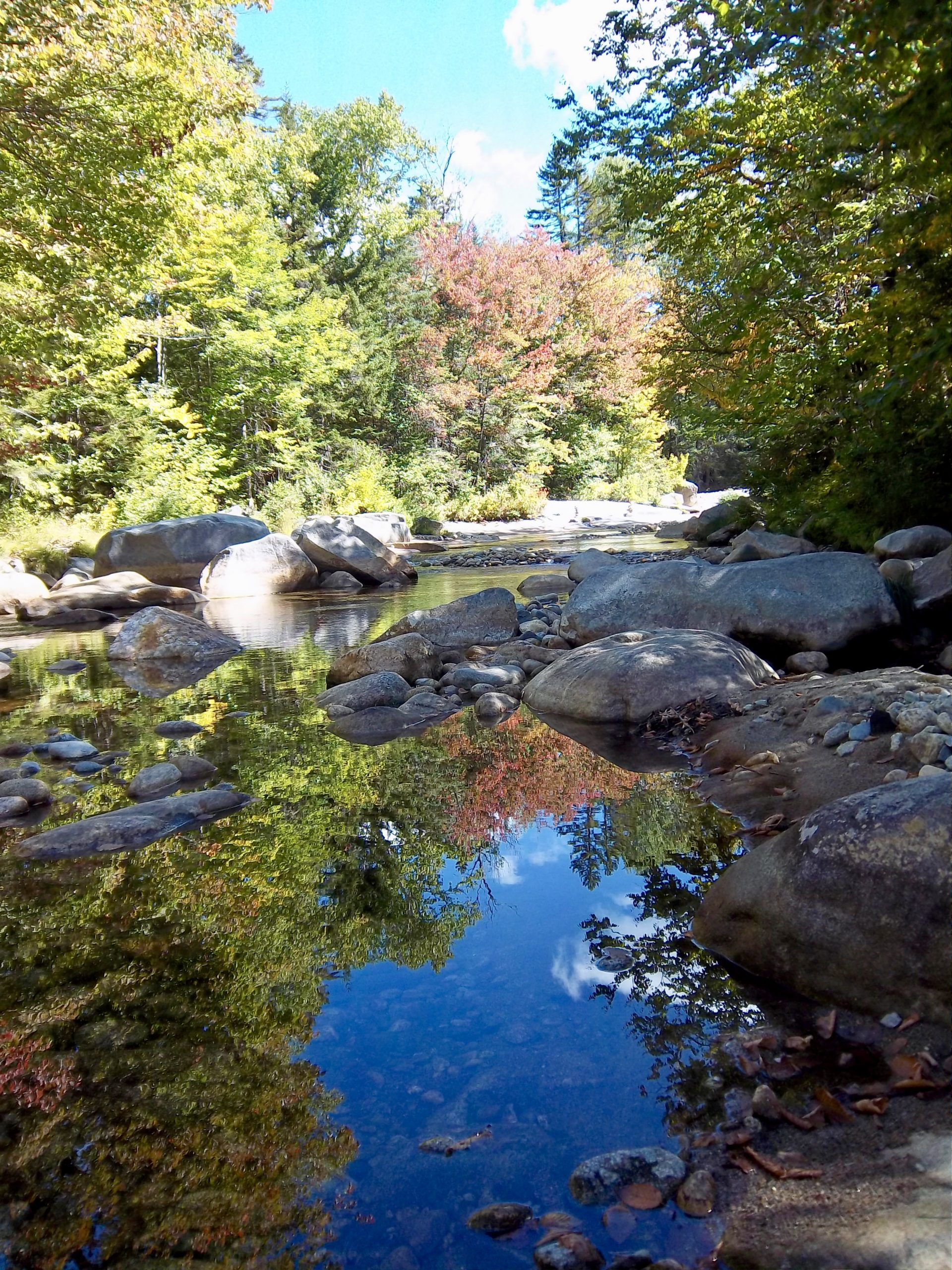 Contest Entry #23 - Reflecting on Fall - Blue sky and fall foliage reflecting on still river water surrounded by boulders with trees in the background