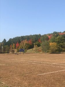 Contest Entry #10 - Time for Football - Dead grass football field with sign and colorful hillside behind